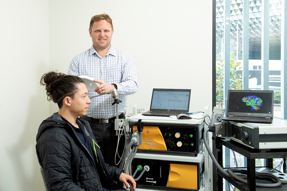 Dr Brenton Hordacre at the UniSA Health and Medical Clinic with his rTMS technology working to tackle post-stroke depression