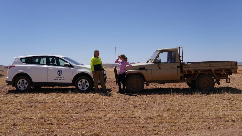 Dr Gunn talking with a farmer on the land