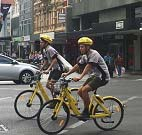 Two cyclists riding Ofo bikes