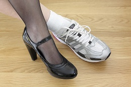 Woman wearing work shoe and gym shoe