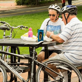 Two older people resting at a picnic table with their bikes