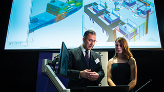 Siemens Business Development Director (Digital Enterprise) Hakan Ozcelik shows the company's advanced Product Lifecycle Management (PLM) software to UniSA student UniSA first-year engineering student Franke Agenbag.