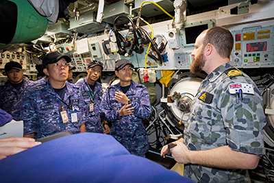 Royal Australian Navy officer Lieutenant Joseph Howell (right) explains the weapon storage compartment to Japan Maritime Self-Defense Force personnel during a tour of HMAS Sheean as part of Exercise Pacific Reach at Fleet Base West, Western Australia. Photo by Royal Australian Navy.