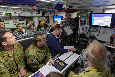 HMAS Farncomb executive officer Lieutenant Commander Benjamin Sweetenham presents an inshore operations brief to guests and crew aboard HMAS Farncomb in Sydney. Photo by Royal Australian Navy.