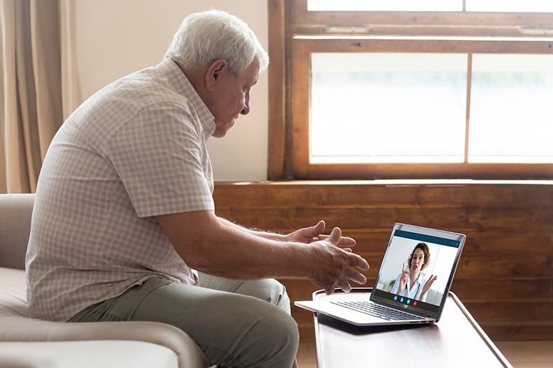 Elderly man video conferencing on a laptop computer